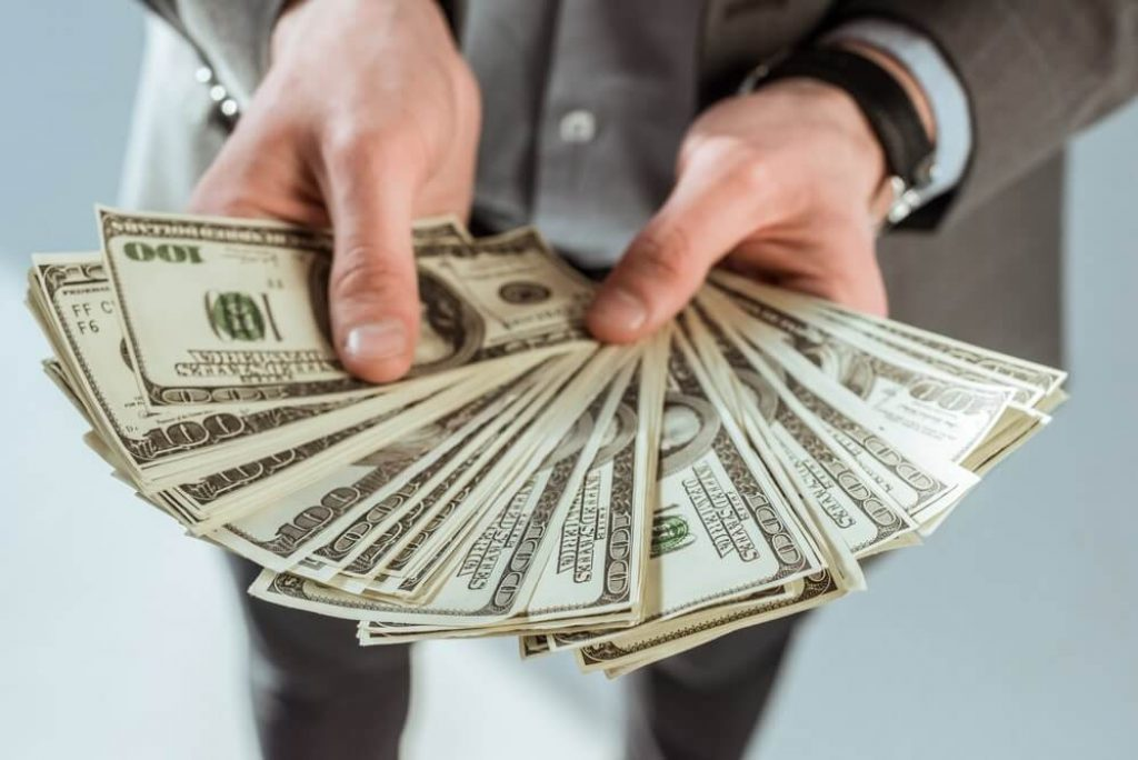 Close-up view of businessman holding dollar banknotes in hands - stock image