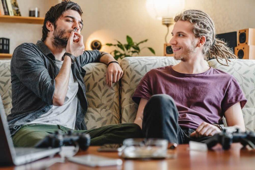 Young caucasian friends smoking marijuana joint at home