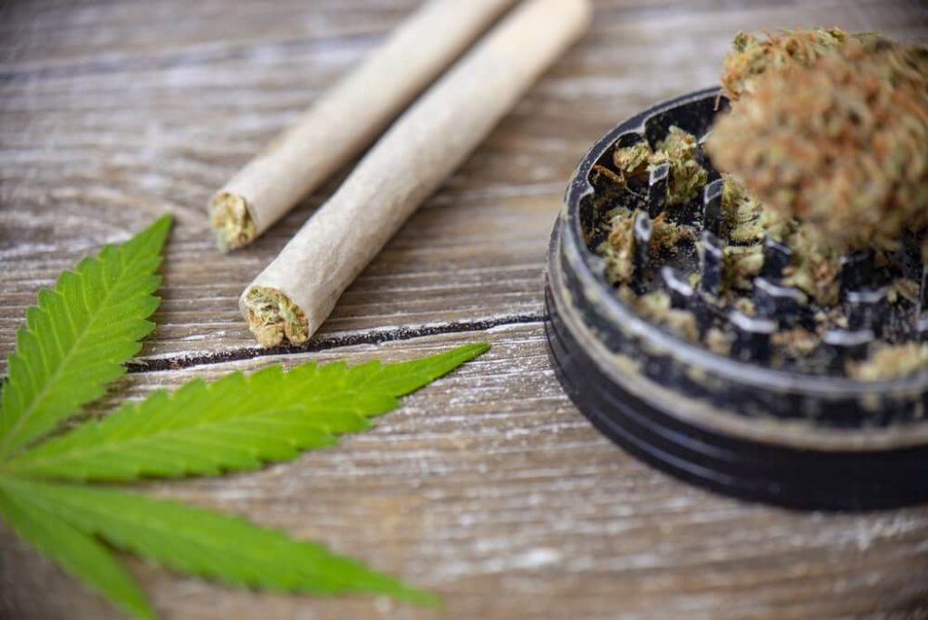 Cannabis joints with rolling paper and grinder over wood background