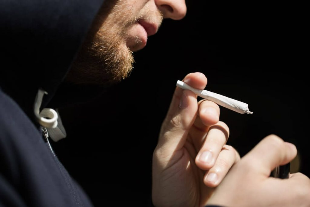 Close up of addict lighting up marijuana joint