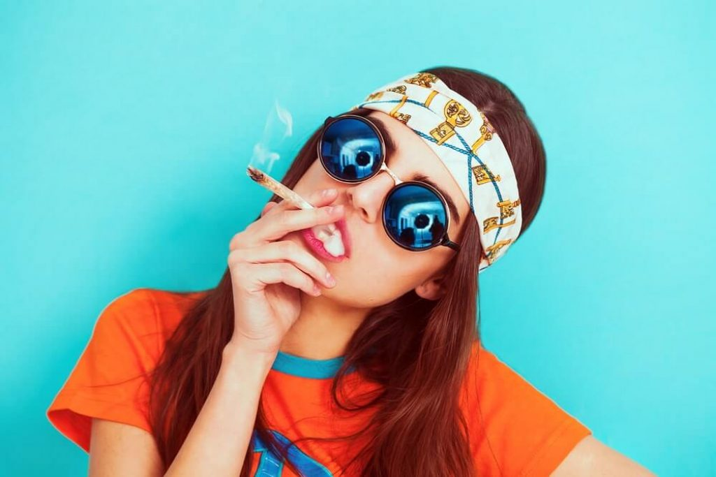 Hippy girl portrait smoking weed and wearing sunglasses