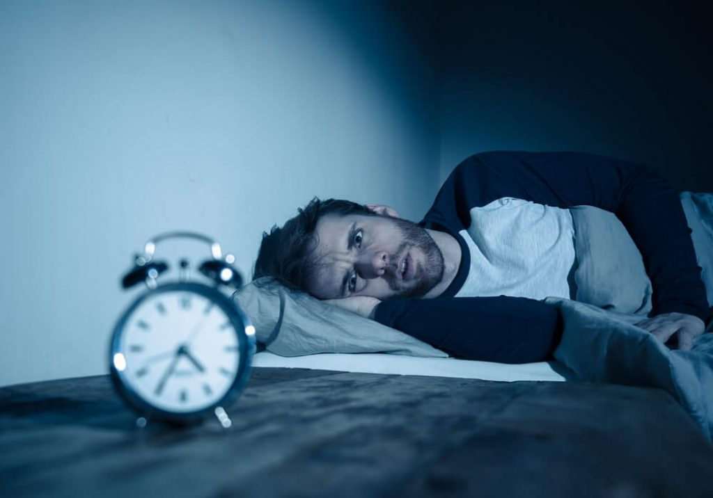 Insomnia Stress and Sleeping disorder concept. Sleepless desperate young caucasian man awake at night not able to sleep, feeling frustrated and worried looking stressed and concerned at alarm clock